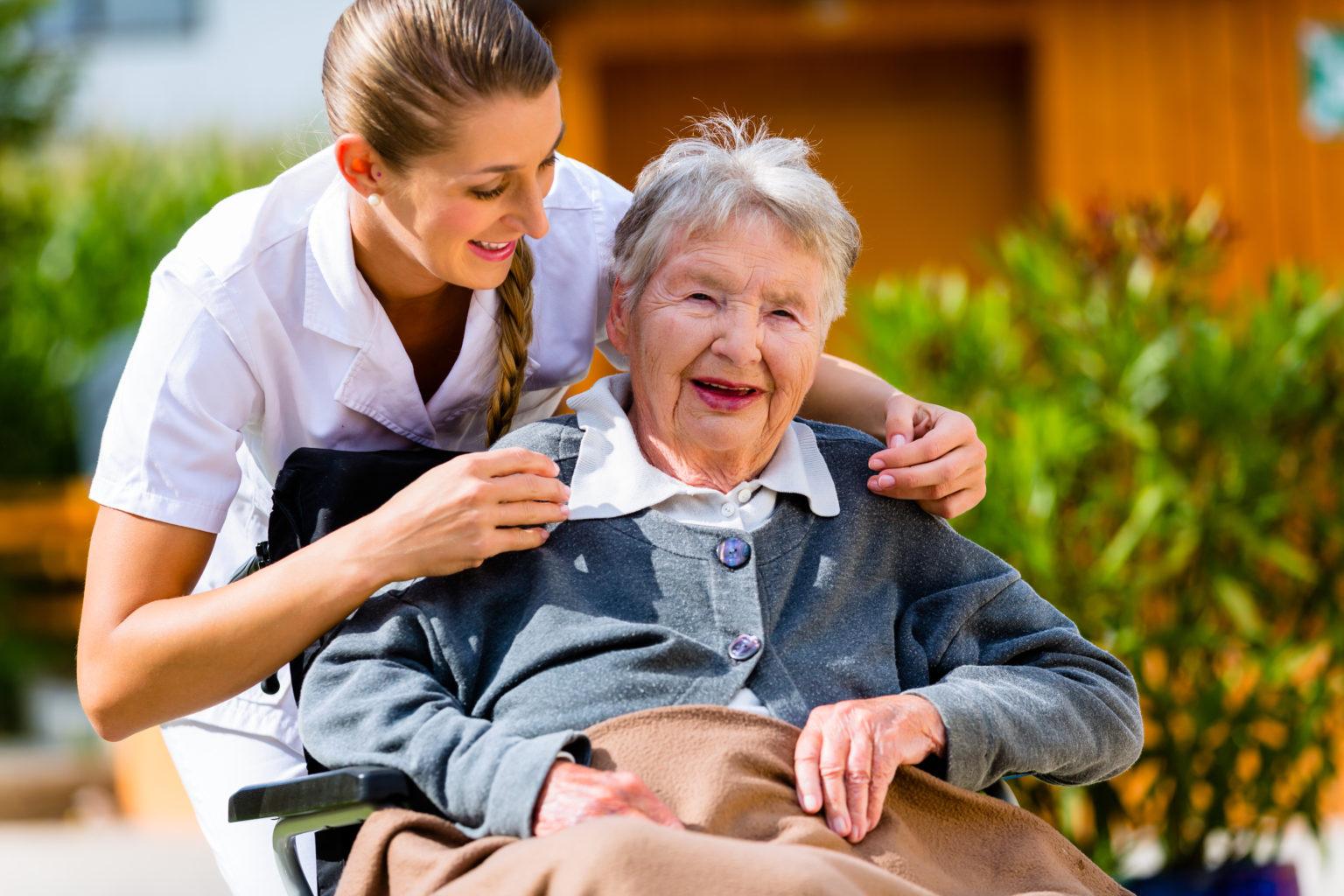 Seniorin mit Altenpflegerin im Garten